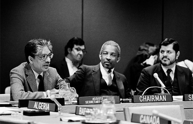 Ad Hoc Committee on Drafting International Convention Against Apartheid in Sports Holds First 1983 Meeting. Seen at the presiding table during the meeting are, from left, Assistant Secretary-General Enuga S. REDDY, Centre Against Apartheid; Committee Chairman Ernest B. MAYCOCK (Barbados); and Committee Secretary Salih ARAIM. 20/Jan/1983. UN Photo/Yutaka Nagata. (Source: United Nations Photo Flickr stream.)